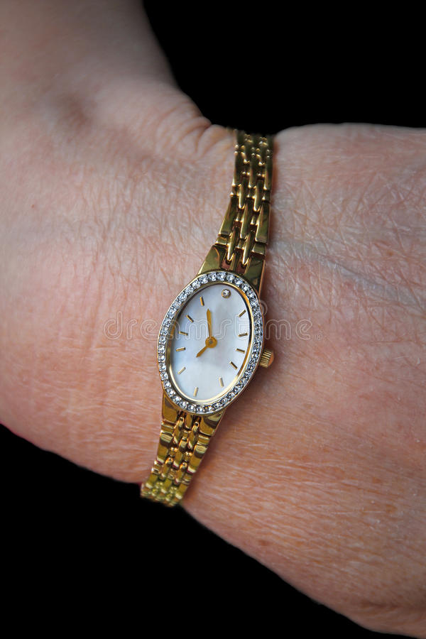 Ladies timepiece gold wrist watch. Photo of a modern ladies gold wrist watch with mother of pearl face with diamontes surrounding clock face royalty free stock photo