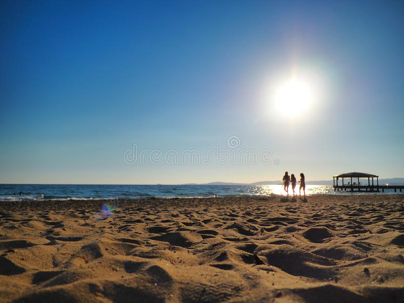 Ladies walking on the beach at sunset in turkey aegean coast.  royalty free stock photography