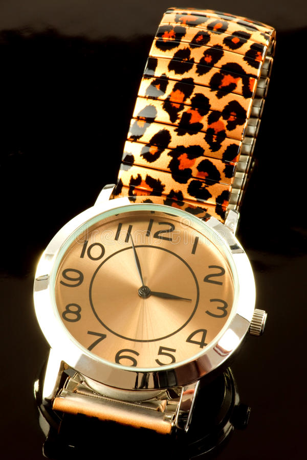 Ladies watch with print strap. Closeup of luxurious ladies watch with animal print strap, black background stock photography