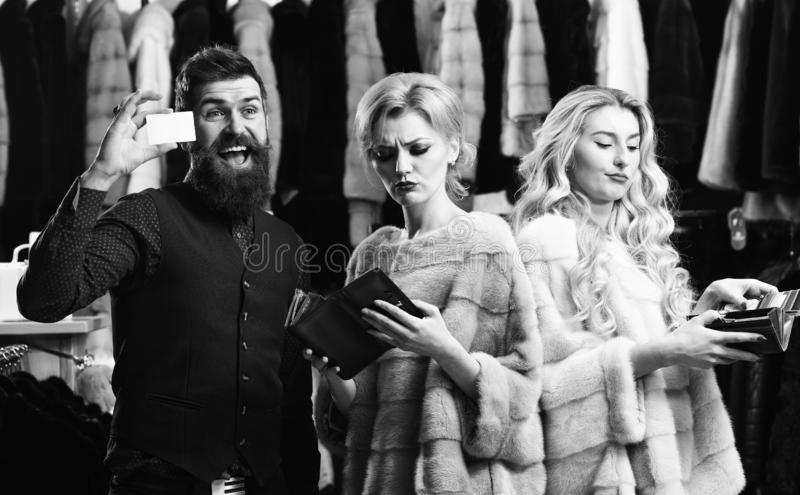 Ladies wear mink fur coats near macho. Luxury shopping concept. Girls shopping in luxury fur store with bearded man. Women in violet and pink fur coats with royalty free stock photography