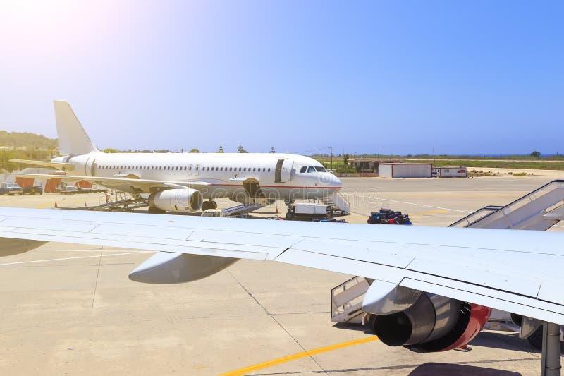 Ladingslading op vliegtuig in luchthaven vóór vlucht mening door de vleugel van een ander vliegtuig royalty-vrije stock afbeelding