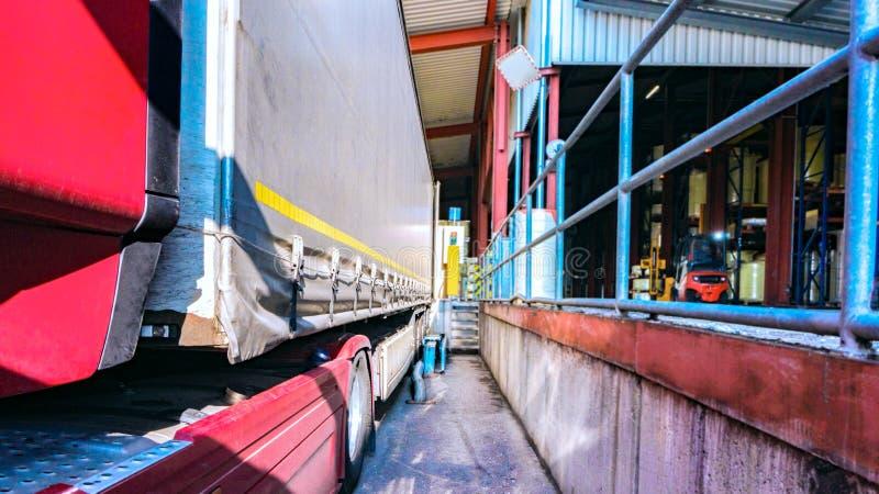 Ladingsvrachtwagen bij de pakhuisbouw de vrachtwagen met de aanhangwagen bij de lading royalty-vrije stock afbeelding