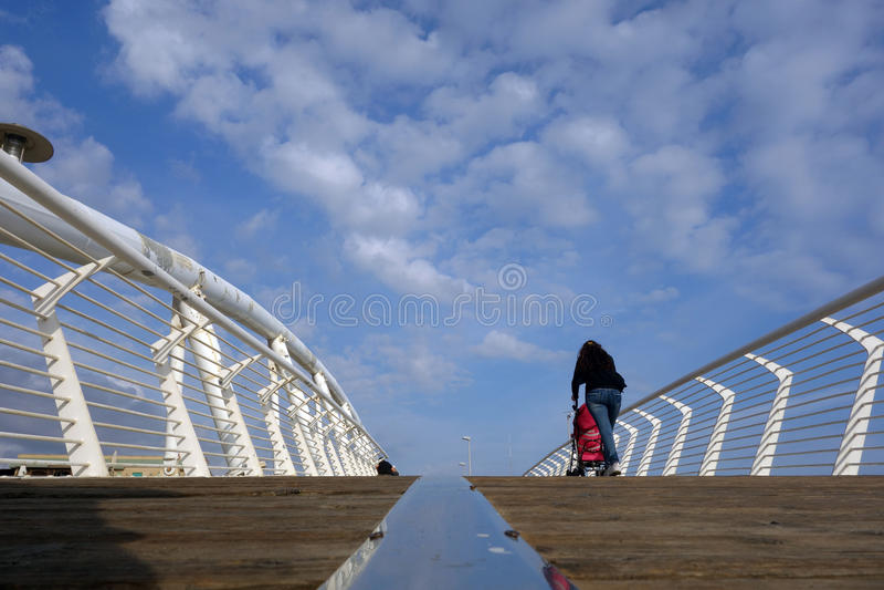 Ladispoli single mother bridge. LADISPOLI, ITALY - JUNE 9, 2016: people walk over the Pedestrian modern Bridge enjoying the seaside royalty free stock photos