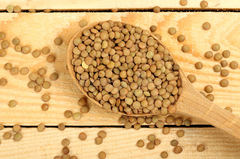 Ladle of lentils. Ladle of uncooked lentils on wooden planks royalty free stock photography