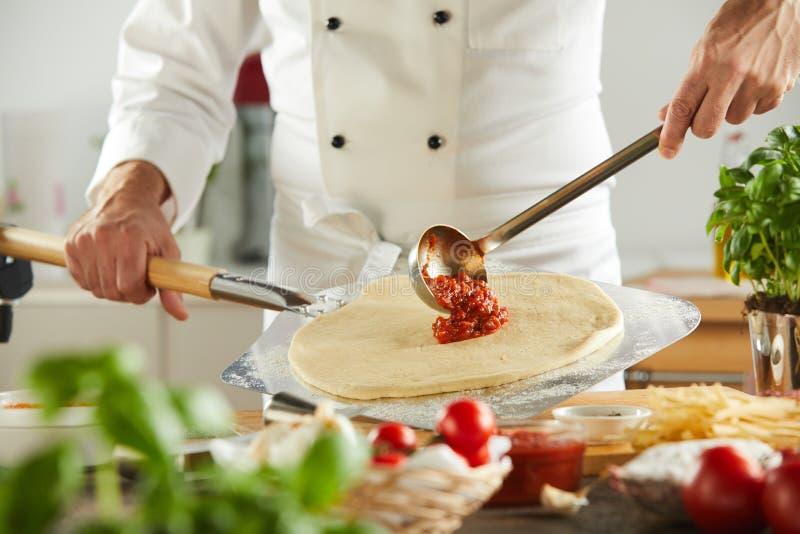 Ladling Tomatenkonzentrat des Chefs auf einen Pizzaboden stockfotografie
