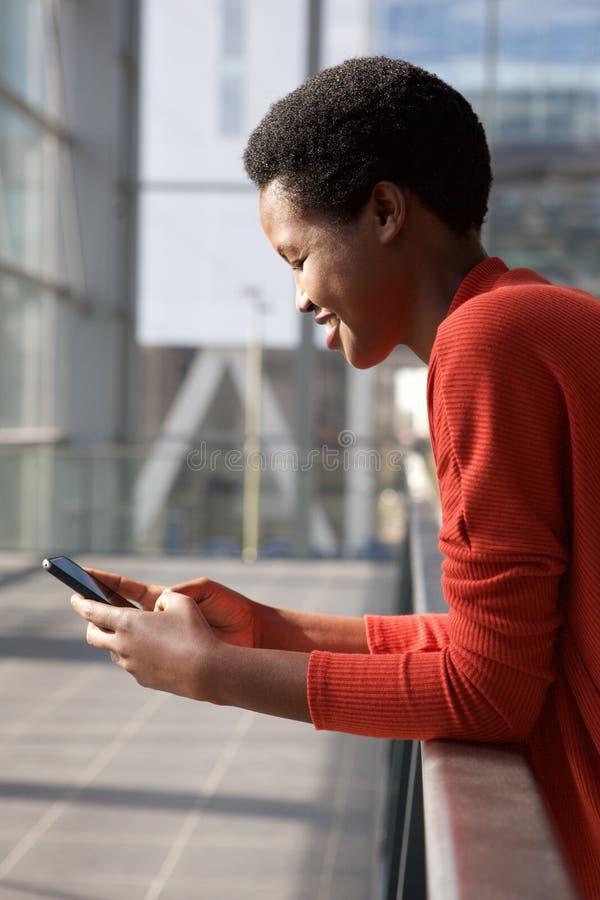 Lado ascendente próximo da mulher afro-americano nova feliz que olha o telefone celular imagem de stock
