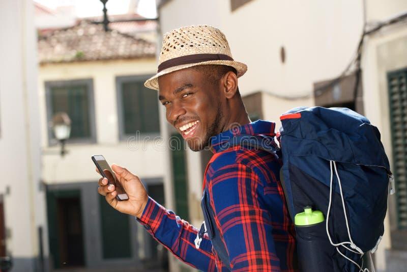Lado ascendente próximo do homem afro-americano feliz com trouxa e telefone celular foto de stock royalty free