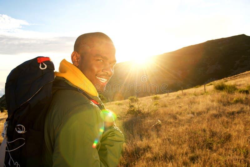 Lado ascendente próximo do homem feliz que caminha nas montanhas com trouxa imagens de stock
