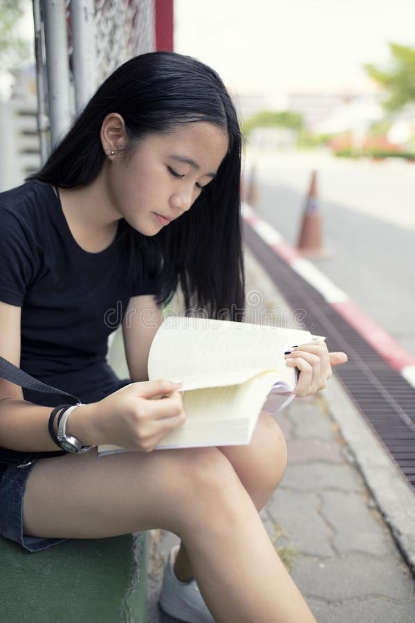 Lado asiático da rua da escola do livro de leitura do adolescente fotos de stock
