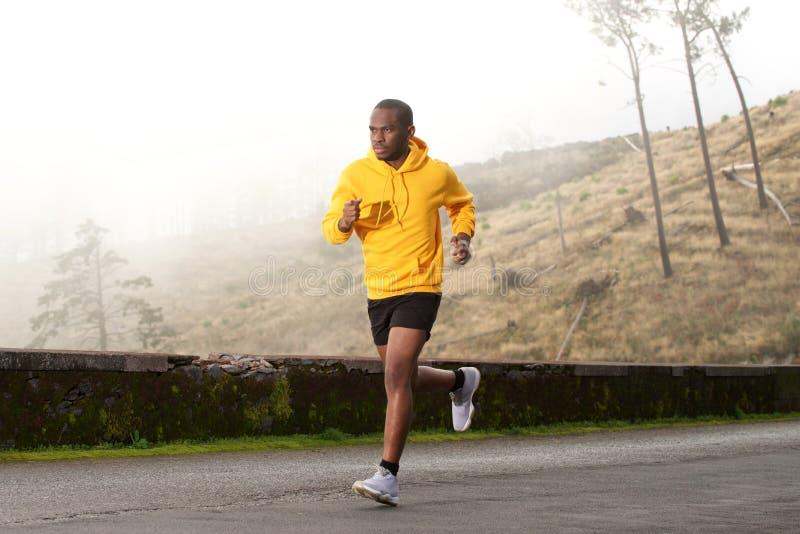 Lado completo do comprimento do homem afro-americano novo saudável que corre na rua foto de stock