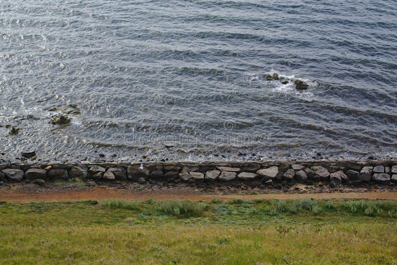 Lado de la playa con las piedras grandes y la hierba verde imagen de archivo libre de regalías
