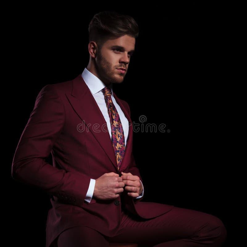 Lado de um homem elegante que abotoa seu terno ao sentar-se imagem de stock