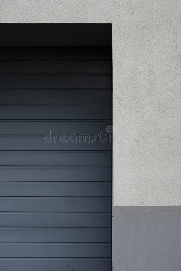 Lado de una puerta del garaje del metal en una pared blanca y gris imagen de archivo
