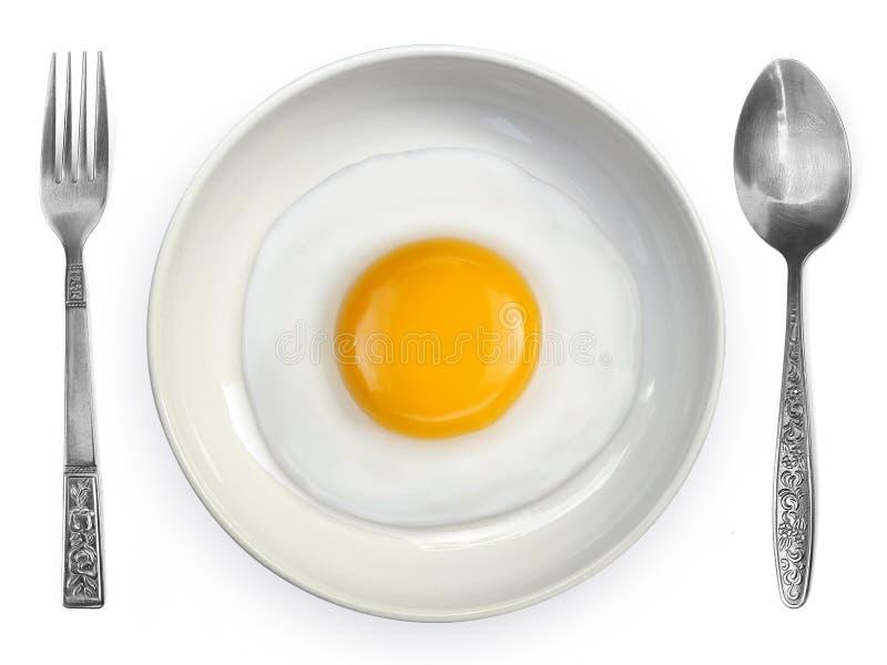 Lado del huevo frito encima de una placa con la cuchara y bifurcación en un fondo blanco fotos de archivo libres de regalías