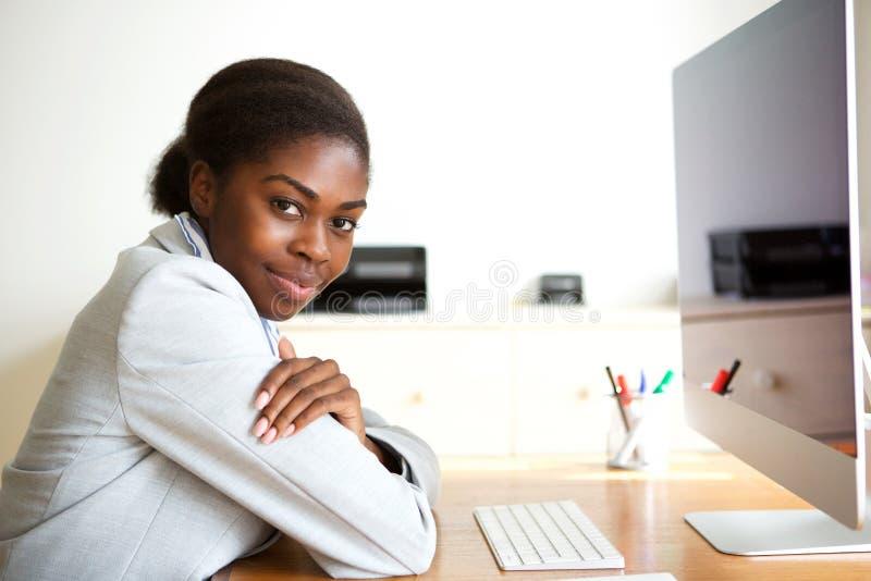 Lado del ordenador afroamericano joven de la compra de la mujer de negocios que se sienta imagenes de archivo