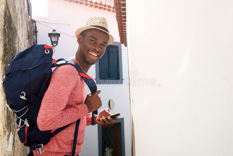 Lado do homem afro-americano de sorriso do curso com trouxa e telefone celular imagens de stock