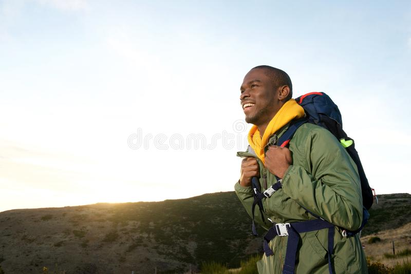 Lado do homem afro-americano feliz que caminha na natureza com trouxa fotografia de stock royalty free