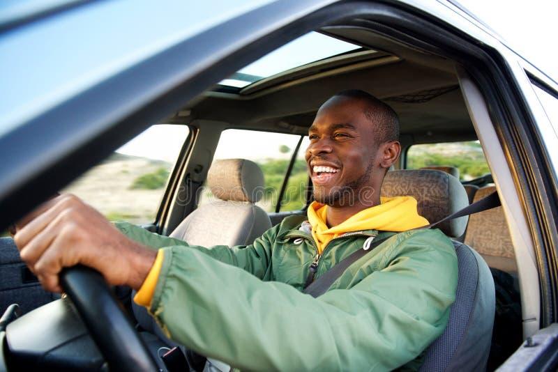 Lado do homem afro-americano feliz que conduz o carro foto de stock royalty free