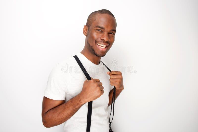 Lado do homem afro-americano feliz que levanta com os suspensórios pelo fundo branco imagem de stock royalty free