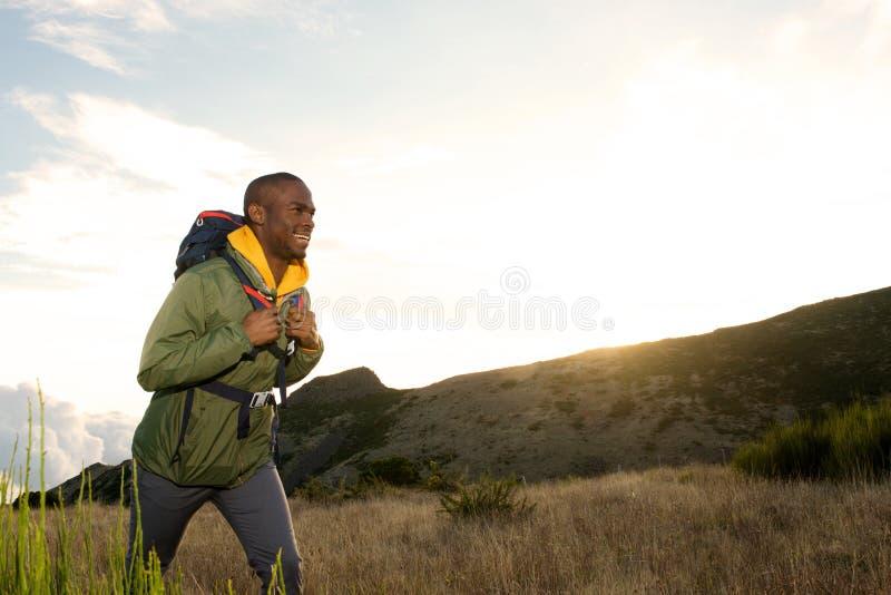Lado do homem afro-americano novo feliz que caminha com a trouxa nas montanhas fotos de stock
