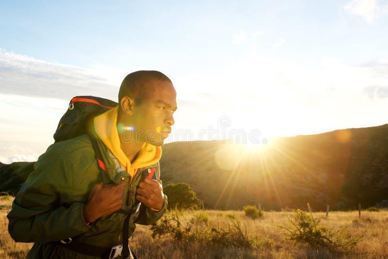 Lado do homem afro-americano que caminha nas montanhas com por do sol no fundo imagem de stock royalty free