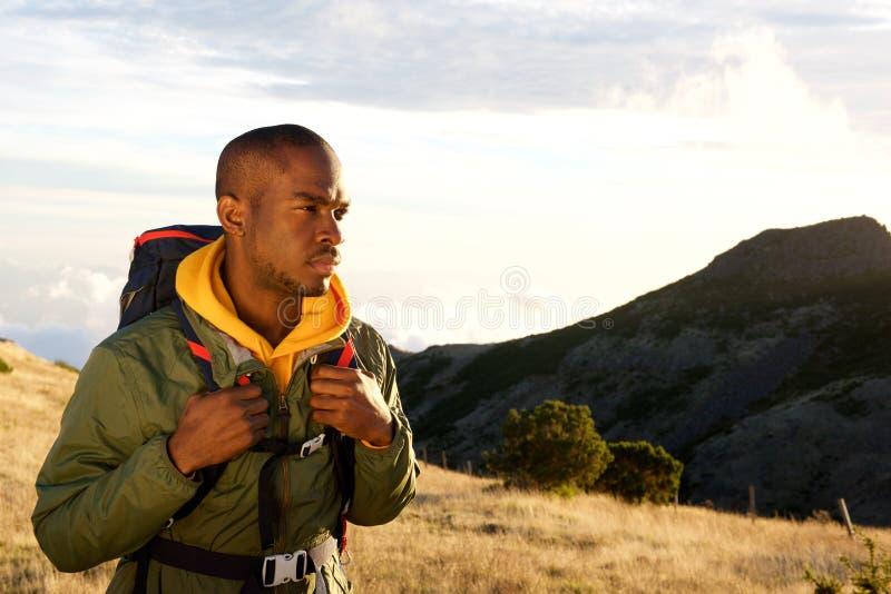 Lado do homem afro-americano que caminha nas montanhas com trouxa fotos de stock