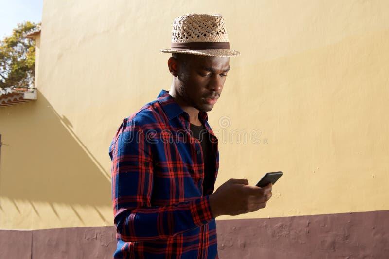 Lado do homem afro-americano que olha o telefone celular fotos de stock royalty free