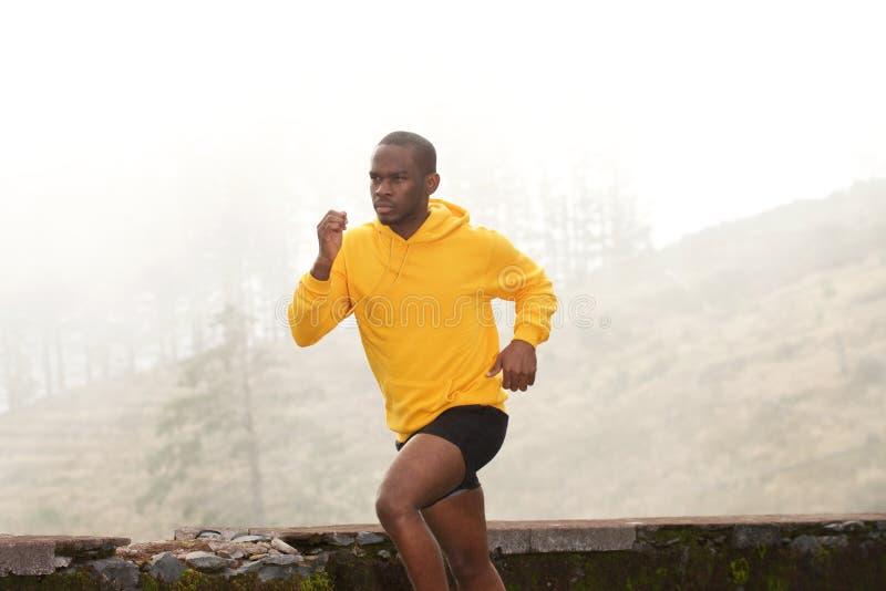 Lado do homem negro novo apto que corre na natureza imagens de stock royalty free