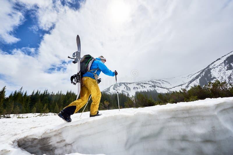 Lado do snowboarder, rosto escondido com um snowboard nas costas, em inclinação de neve Nuvens sobre o céu azul sobre o fundo Âng imagem de stock