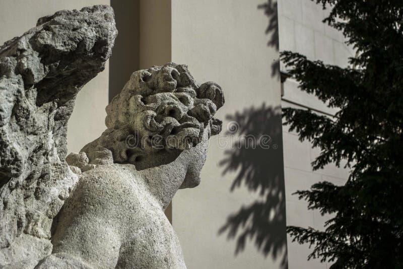 Lado oscuro de una estatua de piedra del ángel cerca de las sombras de la pared imagenes de archivo