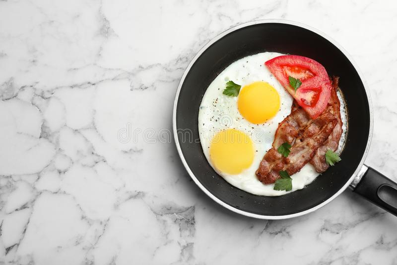 Lado soleado frito encima de los huevos con el tomate y el tocino en cacerola en el fondo de mármol, visión superior foto de archivo