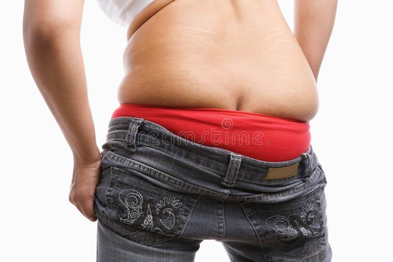 Lado traseiro da mulher gorda que tenta desgastar calças de brim apertadas imagens de stock