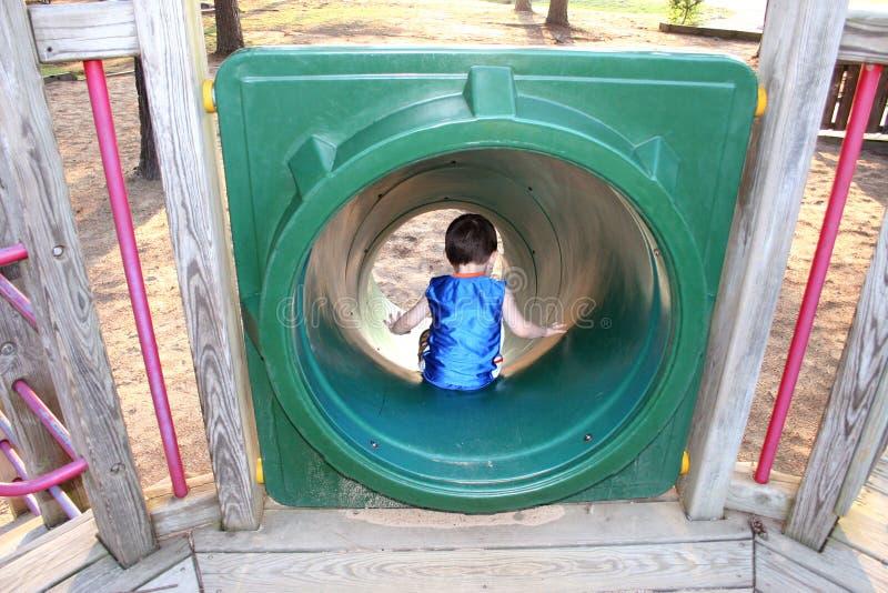 Lado traseiro do menino que vai abaixo da corrediça do parque fotos de stock royalty free