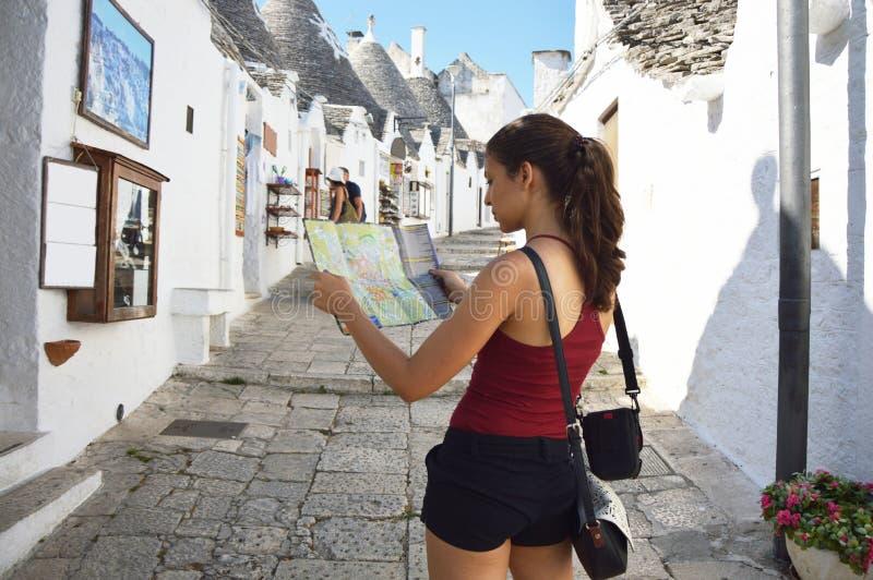 Lado trasero de la muchacha del viajero que busca la dirección correcta en mapa Trulli en la región de Apulia, Italia de Alberobe fotos de archivo libres de regalías