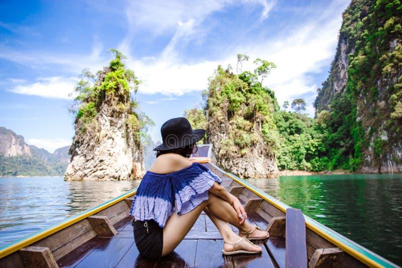 Lado trasero de una mujer que se sienta en el barco de la cola larga foto de archivo