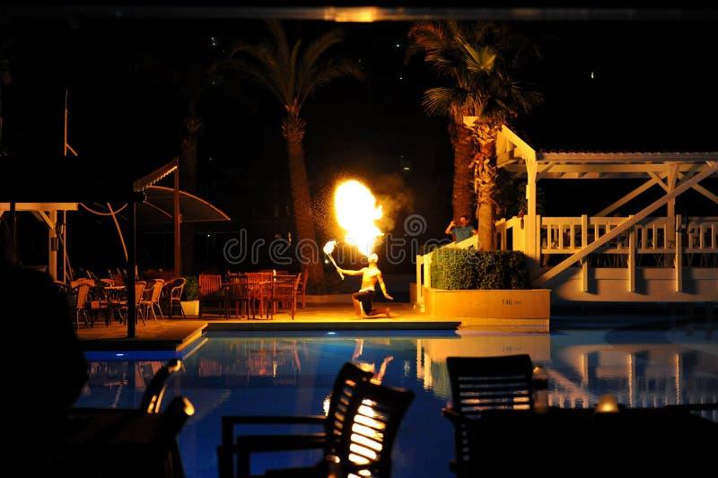 Lado, Turquía - 10 de abril de 2014: El artista de la demostración del fuego respira el fuego en la oscuridad en un hotel de lujo foto de archivo libre de regalías