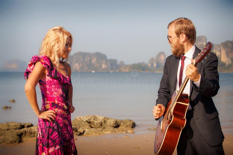 Lado-vista del Blonde y del guitarrista sobre la playa imagen de archivo