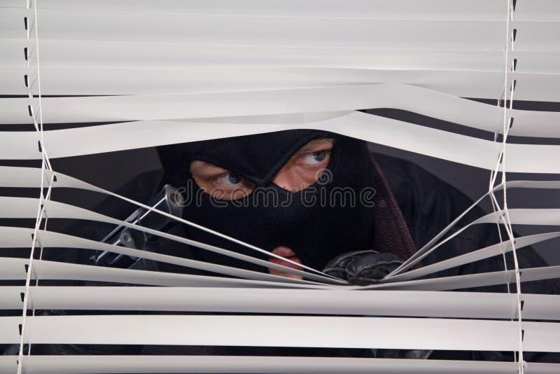 Ladrão com a arma que olha para fora a janela imagens de stock royalty free