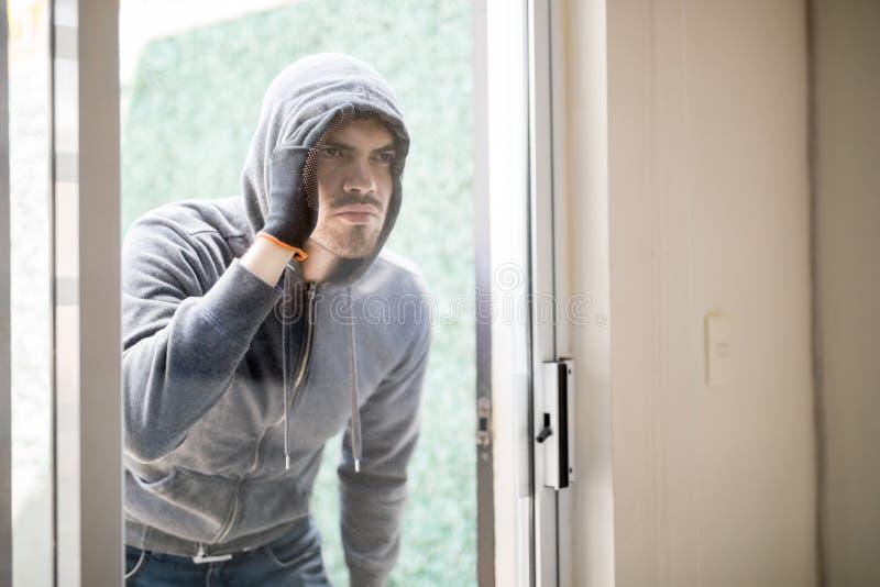 Ladrão da casa que olha dentro de uma casa fotografia de stock