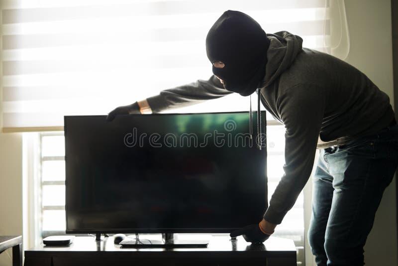 Ladrão da casa que toma uma tevê com ele fotos de stock