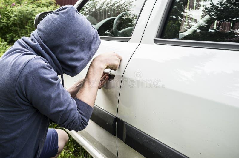Ladrão em um revestimento com uma capa que tenta roubar um carro e quebrar o th imagem de stock