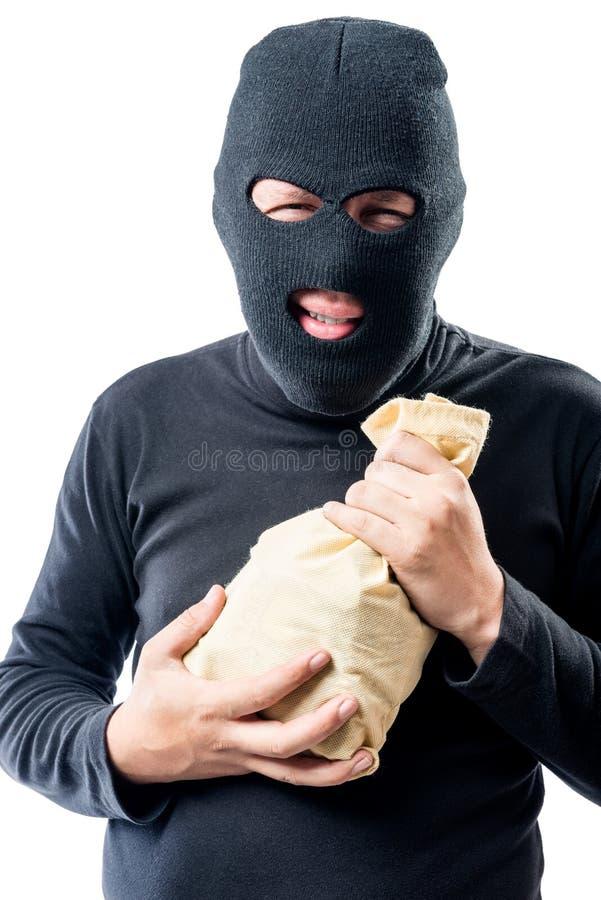 Ladrão em uma máscara com um saco do dinheiro em um branco fotos de stock