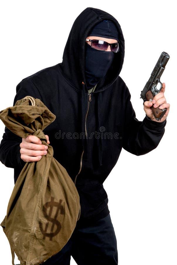 Ladrão encapuçado com uma arma e um saco imagens de stock