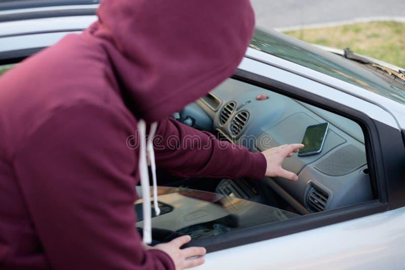 Ladrão encapuçado que rouba um portátil do computador de um carro estacionado fotos de stock royalty free