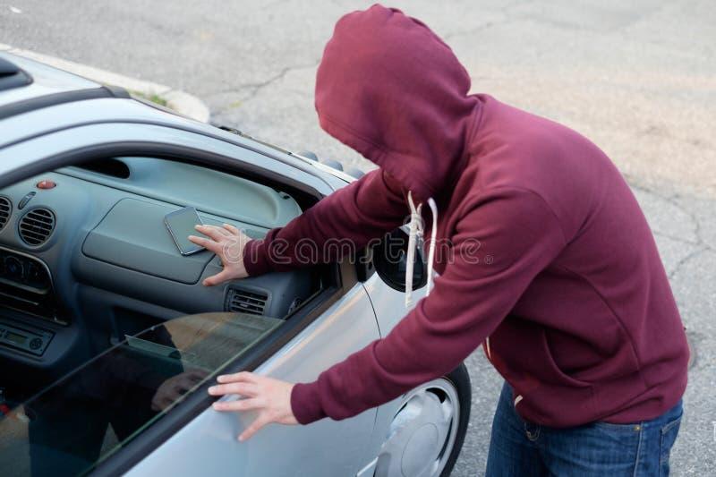 Ladrão encapuçado que rouba um telefone esperto do telefone de um carro estacionado fotografia de stock royalty free