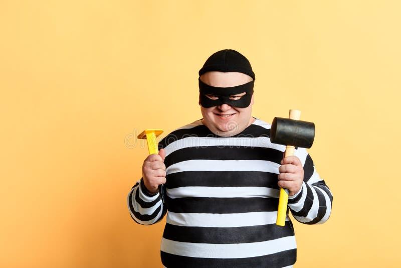 Ladrão gordo com posição do martelo isolado no fundo amarelo imagens de stock