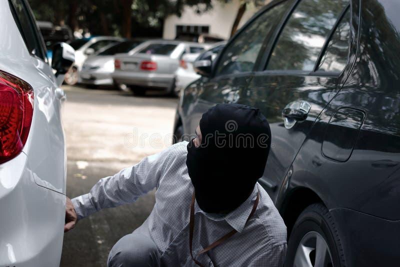 Ladrão mascarado em um passa-montanhas pronto para roubar o carro do automóvel Conceito da extorsão e do crime foto de stock