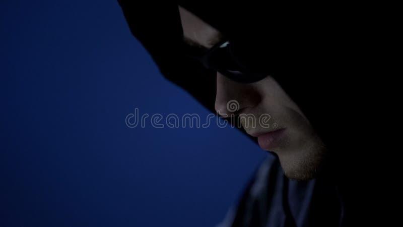 Ladrão masculino no hoodie e nos óculos de sol, preparação antes da ofensa, ascendente próximo da cara fotos de stock royalty free