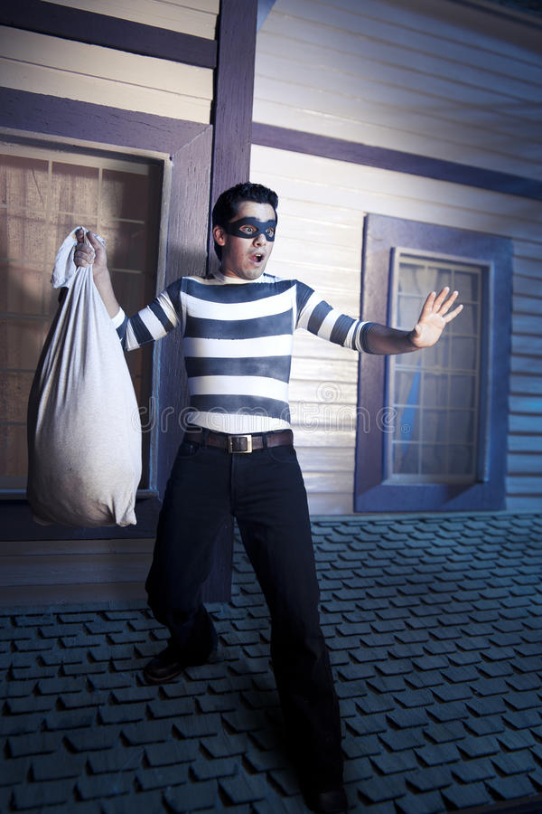Ladrão no telhado de uma casa na noite fotos de stock
