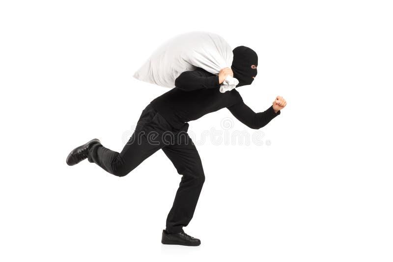 Ladrão que carreg um saco e um corredor afastado fotografia de stock